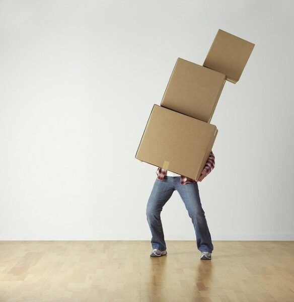 person holding 3 stacked boxes